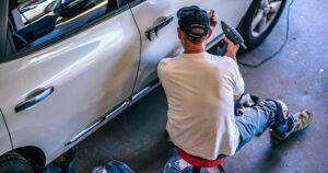 Mann som reparerer bil. Foto.